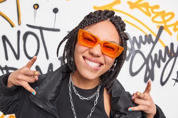 Funky teenage girl of street gang makes cool gesture bites lower lip has braids wears orange sunglasses fashionable black jacket has fun at public place poses against graffiti wall has playful mood