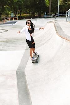 スケートパークでロングボードに乗ってファンキーな若い女の子のティーンエイジャー