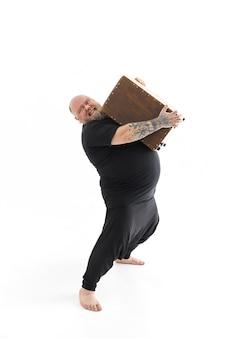 Funn caucasian bearded tattoed man is posing on white background