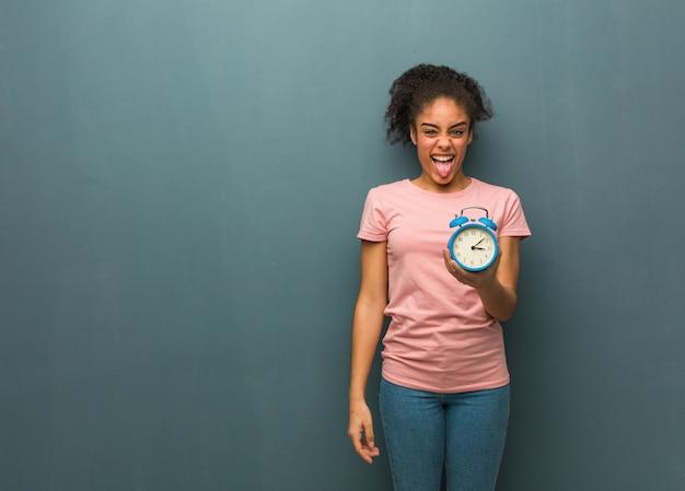 若い黒人女性funnnyとフレンドリーな表示舌。彼女は目覚まし時計を持っています。