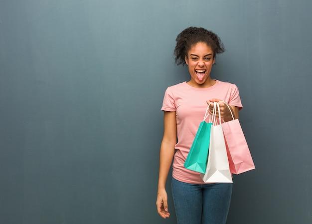 若い黒人女性funnnyとフレンドリーな表示舌。彼女は買い物袋を持っています。