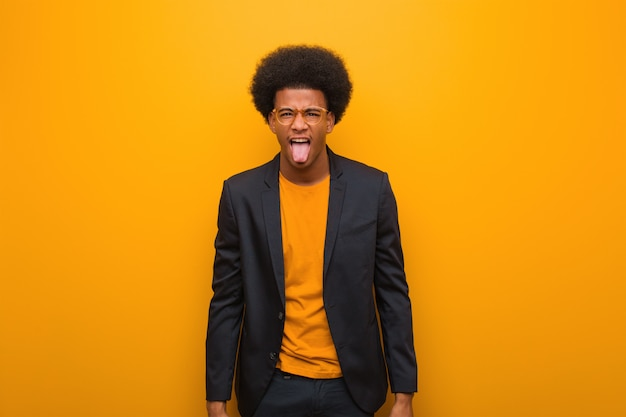 Молодой человек афроамериканца дела над оранжевой стеной funnny и дружелюбно показывая язык