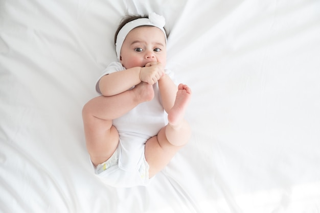 Funny 6 months baby girl playing with legs, lying on bed at home on white bedding. top view.