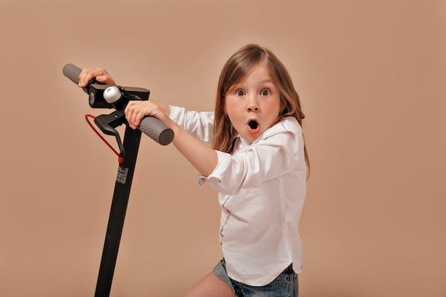 Смешная очаровательная маленькая девочка в белой рубашке с электросамокатом позирует с удивленными эмоциями