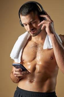 Забавный очаровательный мужчина с мускулистым телом, глядя на экран смартфона на желтом фоне