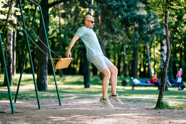 Funny adult bald man in sunglasses jumping from swing on ground in motion.
