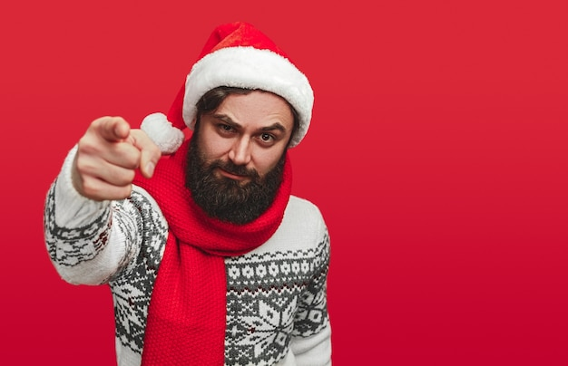 Funny adult bearded male in warm sweater and santa hat