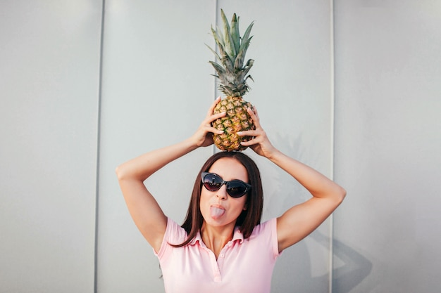 Funny adult girl stands and holds pineapple on her head. she wears sunglasses. woman shows her tongue.