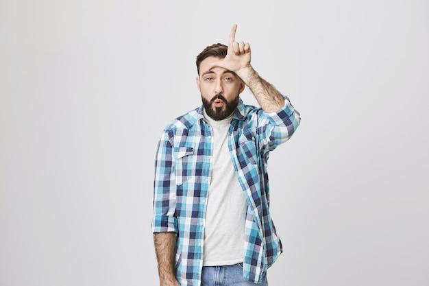 Забавный взрослый мужчина показывает знак проигравшего на лбу и насмехается над человеком