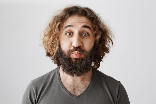 ひげのキスのためにふくれっ面して面白い大人の中東男