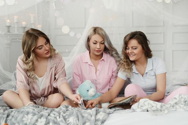 Смешные взрослые женщины, устраивающие пижамную вечеринку.