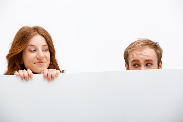 面白い大人赤毛の男と女がテーブルの後ろに隠れて