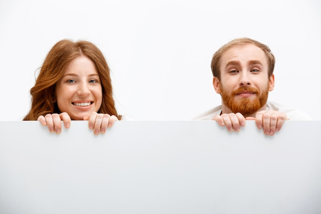 Funny adults redhead man and woman hiding behind table
