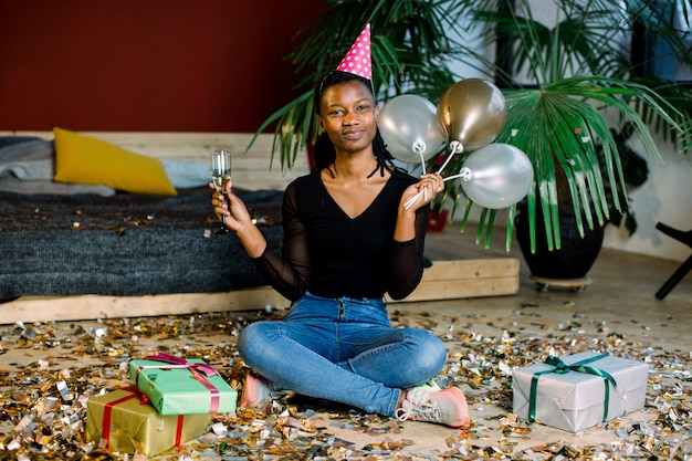 Funny african american girl in birthday hat and with air balloons sitting on the floor with present boxes gifts and confetti. celebration, party concept