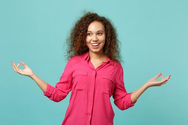 カジュアルな服装で面白いアフリカ系アメリカ人の女の子は、青いターコイズブルーの壁の背景に分離された瞑想をリラックスしてヨガのジェスチャーで手を握ります。人々の誠実な感情、ライフスタイルのコンセプト。コピースペースをモックアップします。