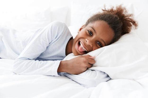 Забавная афроамериканская маленькая девочка улыбается и лежит в постели у себя дома