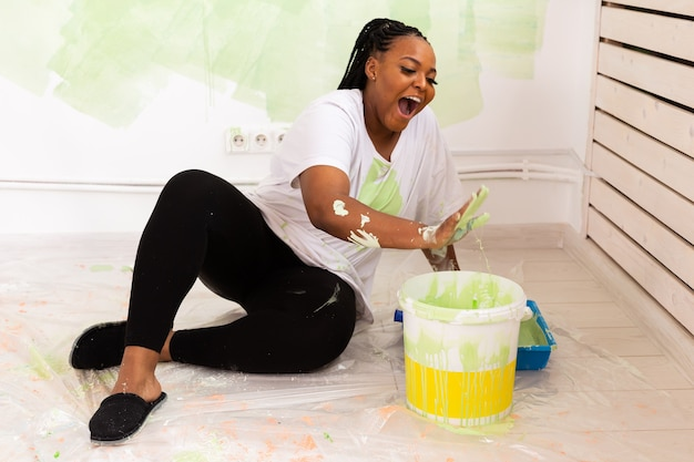 Funny african american woman painting wall in her new apartment. renovation, redecoration and repair