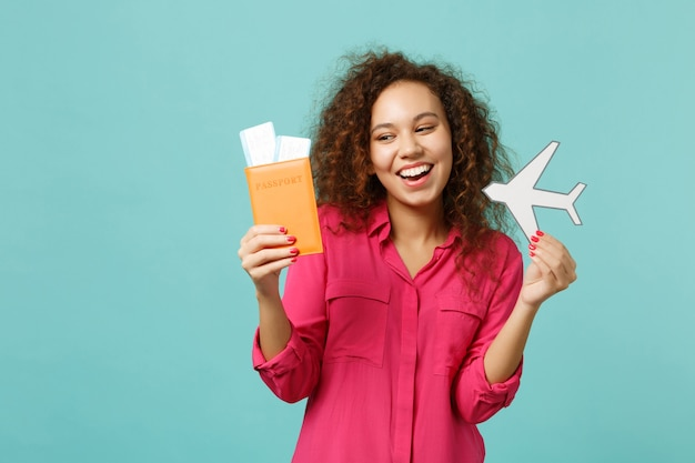 Funny african girl in casual clothes holding passport, boarding pass ticket, paper airplane isolated on blue turquoise wall background. people sincere emotions, lifestyle concept. mock up copy space.