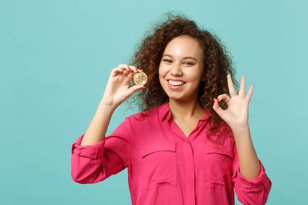 Funny african girl in casual clothes showing ok gesture, holding bitcoin future currency isolated on blue turquoise background in studio. people sincere emotions lifestyle concept. mock up copy space.