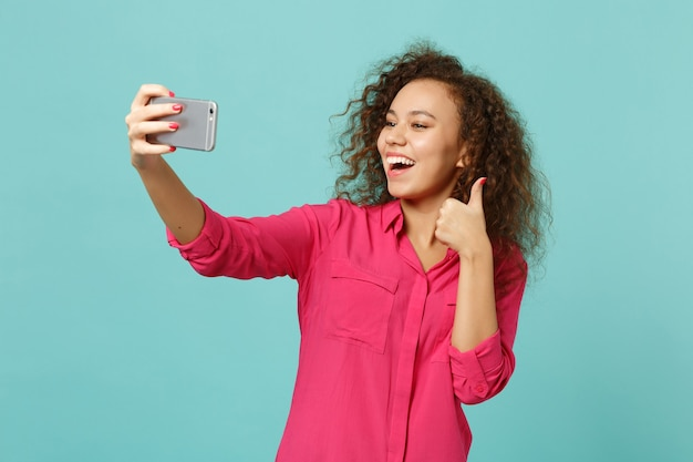 Funny african girl in casual clothes showing thumb up doing selfie shot on mobile phone isolated on blue turquoise background in studio. people sincere emotions, lifestyle concept. mock up copy space.