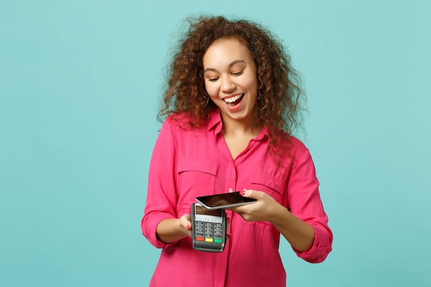 Funny african girl hold mobile phone wireless modern bank payment terminal to process, acquire credit card payments isolated on blue turquoise background. people lifestyle concept. mock up copy space.