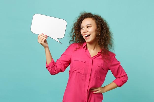 Смешная африканская девушка в повседневной одежде, держащая пустой бланк скажите облако, речевой пузырь, изолированный на синем бирюзовом стенном фоне в студии. концепция образа жизни искренние эмоции людей. копируйте пространство для копирования.
