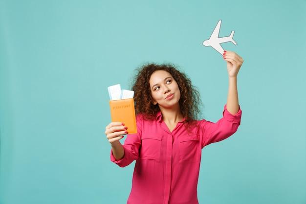 여권, 탑승권, 파란색 청록색 벽 배경에 격리된 종이 비행기를 들고 캐주얼 옷을 입은 재미있는 아프리카 소녀. 사람들은 진심 어린 감정 라이프 스타일 개념입니다. 복사 공간을 비웃습니다.