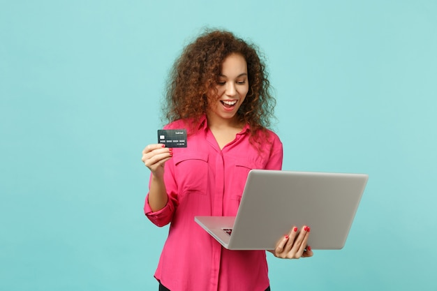 スタジオで青いターコイズブルーの背景に分離されたクレジット銀行カードを保持し、ラップトップpcコンピューターを使用してカジュアルな服装で面白いアフリカの女の子。人々の誠実な感情のライフスタイルの概念。コピースペースをモックアップします。