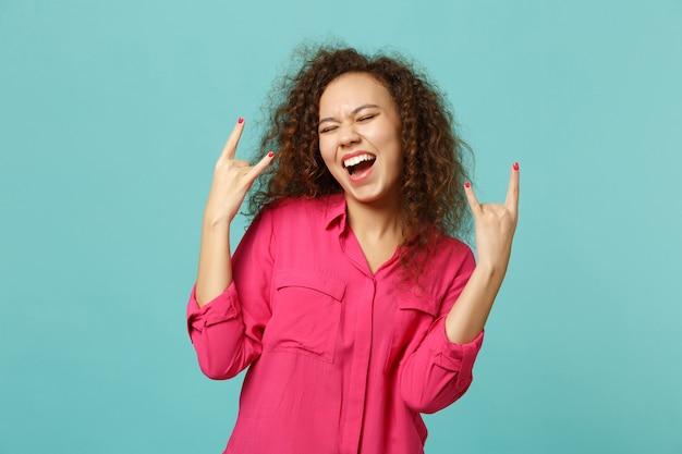 Ragazza africana divertente in abiti casual rosa che tiene gli occhi chiusi, mostrando le corna sul gesto isolato su sfondo blu turchese in studio. concetto di stile di vita di emozioni sincere della gente. mock up copia spazio.