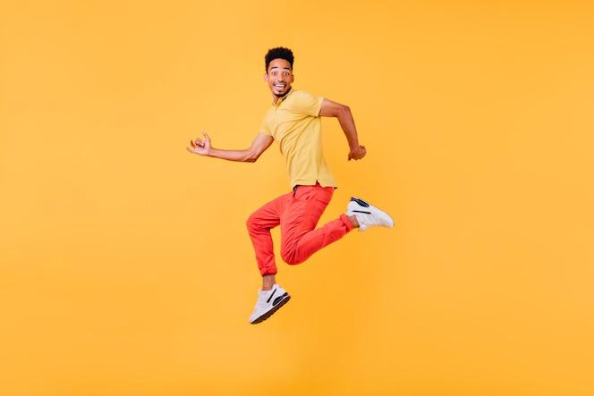 驚いた笑顔でポーズをとる面白いアフリカの男性モデル。ジャンプするスポーティな黒人男性の屋内写真。