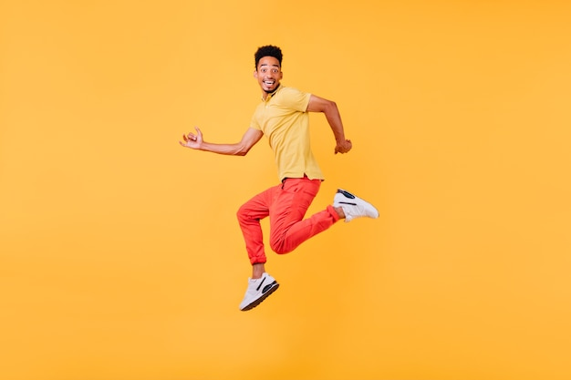 Funny african male model posing with surprised smile. indoor photo of sporty black man jumping.