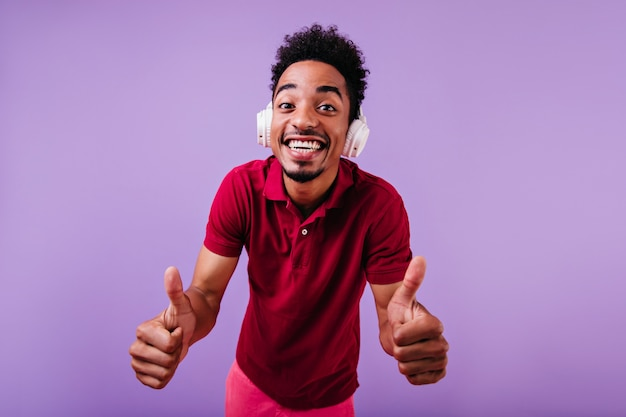 장난 치는 물결 모양의 머리를 가진 재미있는 아프리카 모델. 큰 헤드폰에 잘 생긴 남자 학생의 실내 사진.