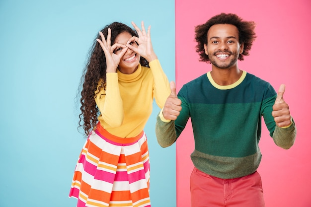 楽しんで、親指を立てて面白いアフリカの若いカップル