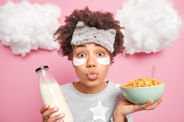 面白いアフロアメリカ人の女の子は、上に白い雲のあるピンクの壁にナイトウェアのポーズを着て健康的な朝食をとるために唇を丸く保ちます