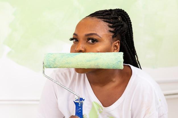 アパートを描いている面白いアフロアメリカ人女性。改修、修理、改装のコンセプト。