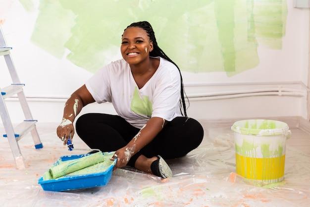 Смешная афро-американская женщина красит квартиру. ремонт, ремонт и концепция косметического ремонта.