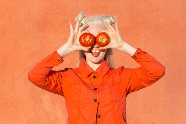 Смешная молодая женщина-альбинос в красной блузке на красном фоне. она держит два красных помидора перед его глазами и показывает ему язык фото высокого качества