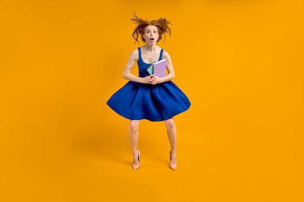 파란 드레스를 입은 재미있는 교사 여성이 하이힐을 신은 학생들에게 충격을 받아 책을 손에 들고 있습니다...