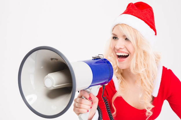 Funny amusing blonde woman in santa claus costume and hat screaming in speaker over white background