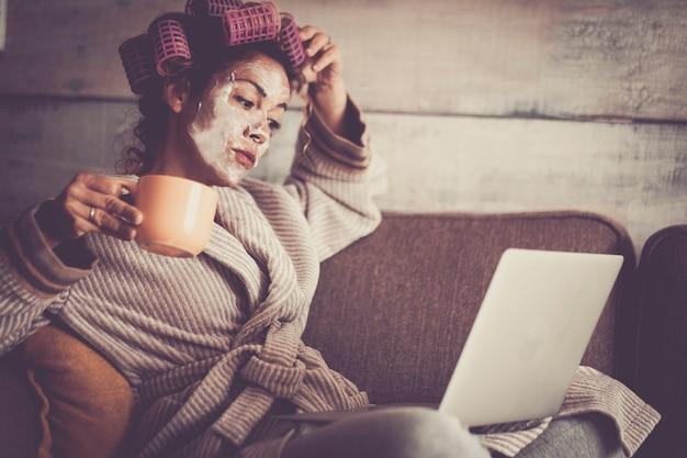 完璧な巻き毛のお茶をリラックスするためのヘアカーラーと一緒に家で面白くて美しい女性