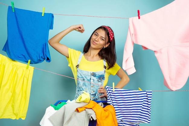 青い背景に分離された家事をしている面白くて美しい主婦。洗濯された服に囲まれた若い白人女性。家庭生活、明るいアートワーク、ハウスキーピングのコンセプト。ヒーローのようにポーズをとる。