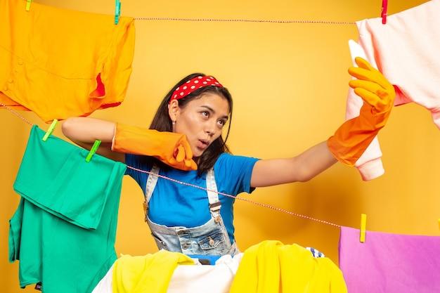 黄色の背景で隔離の家事をしている面白くて美しい主婦。洗濯された服に囲まれた若い白人女性。家庭生活、明るいアートワーク、ハウスキーピングのコンセプト。自撮り写真を作る。