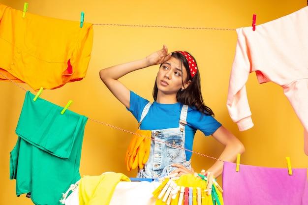 黄色の背景で隔離の家事をしている面白くて美しい主婦。洗濯された服に囲まれた若い白人女性。家庭生活、明るいアートワーク、ハウスキーピングのコンセプト。悲しくて疲れた。