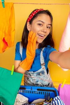 黄色の背景で隔離の家事をしている面白くて美しい主婦。洗濯された服に囲まれた若い白人女性。家庭生活、明るいアートワーク、ハウスキーピングのコンセプト。自分撮りビュー。