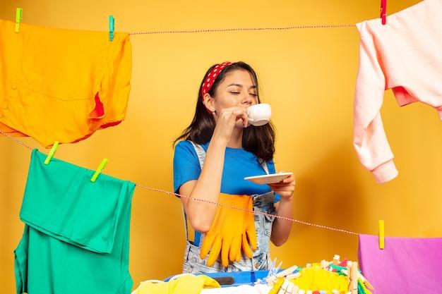 Смешная и красивая домохозяйка делает работу по дому на желтом