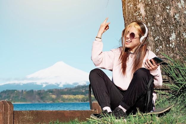 Смешная и веселая девочка слушает музыку со своего мобильного телефона, сидя на скейтборде под деревом.