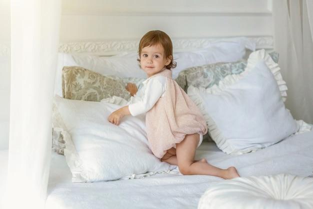 재미 있고 귀여운 갈색 머리 웃는 소녀 밝은 침실에서 침대에서 점프를 재생합니다. 큰 침대가 있는 흰색 인테리어. 어린 시절, 유치원, 청소년, 휴식 개념