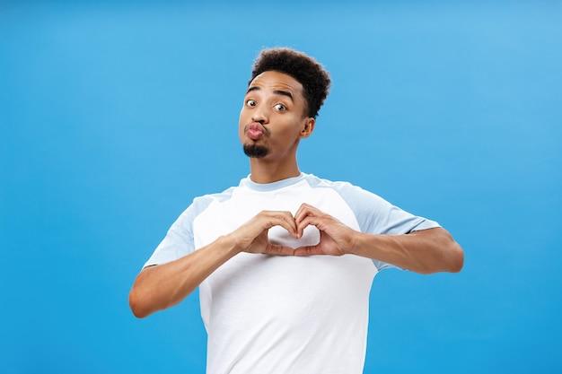 Забавный и милый темнокожий юный студент в футболке, складывая губы в мвах или целуя, показывая сердечко г ...