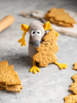 クリスマスツリーの形をしたジンジャーブレッドクッキーを盗む黄色い耳を持つ面白いとかわいいおもちゃのネズミ(2020年のシンボル)は、クリスマスと新年のカード、冬として使用できます。