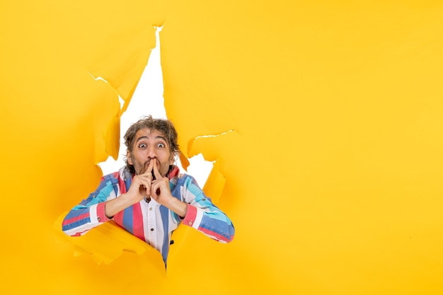引き裂かれた黄色の紙の穴の背景で面白いと感情的な若い男のポーズ